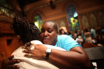 NEW YORK, NY - JULY 14:  People hug during services at Middle Collegiate Church in Manhattan honoring Trayvon Martin on July 14, 2013 in New York City. George Zimmerman was acquitted of all charges in the shooting death of Martin July 13 and some congregants wore hoodies during the service to honor Martin.  (Photo by Mario Tama/Getty Images) ORG XMIT: 173735708